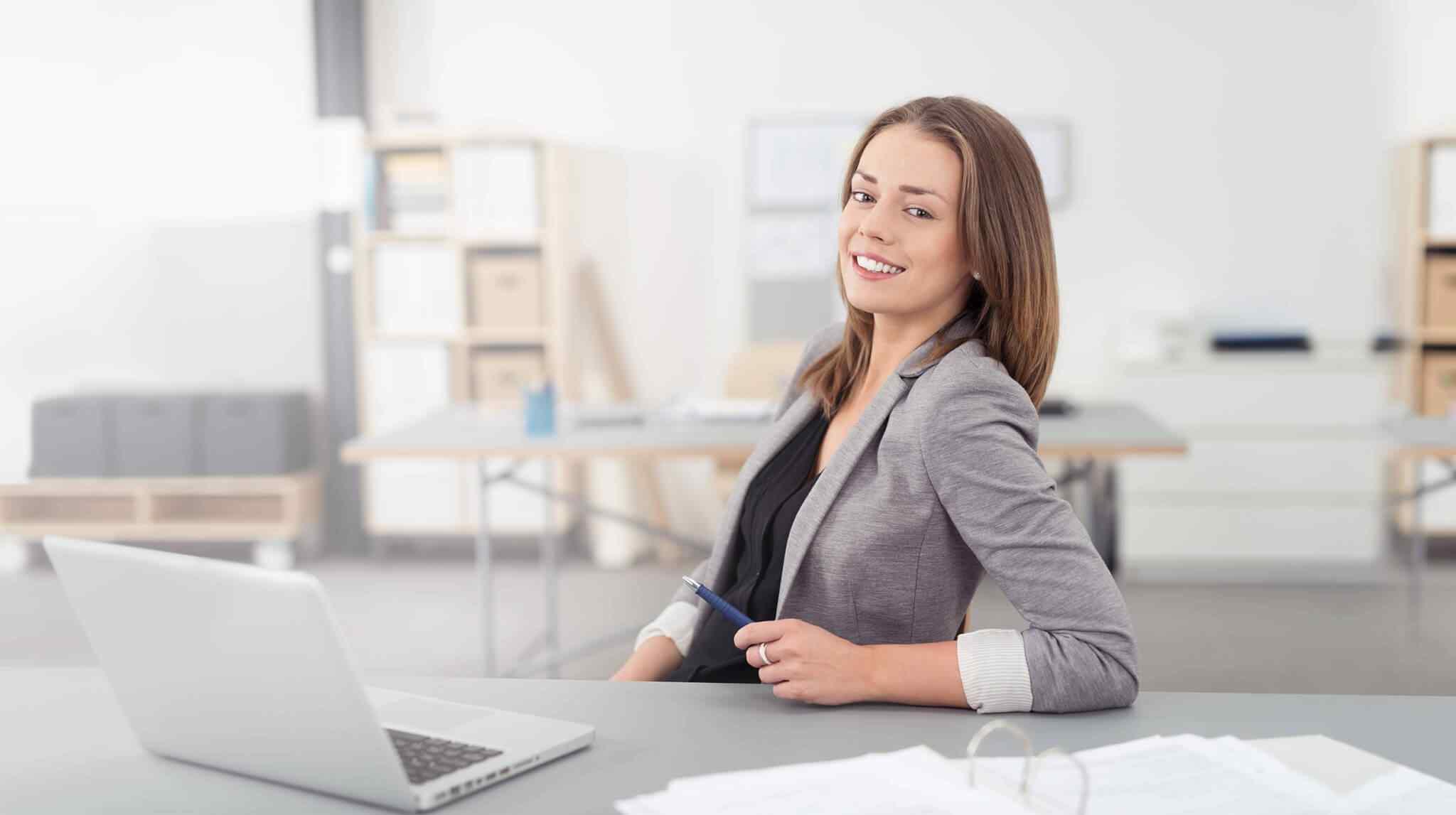 Mulher de terno sorrindo em frente a um computador