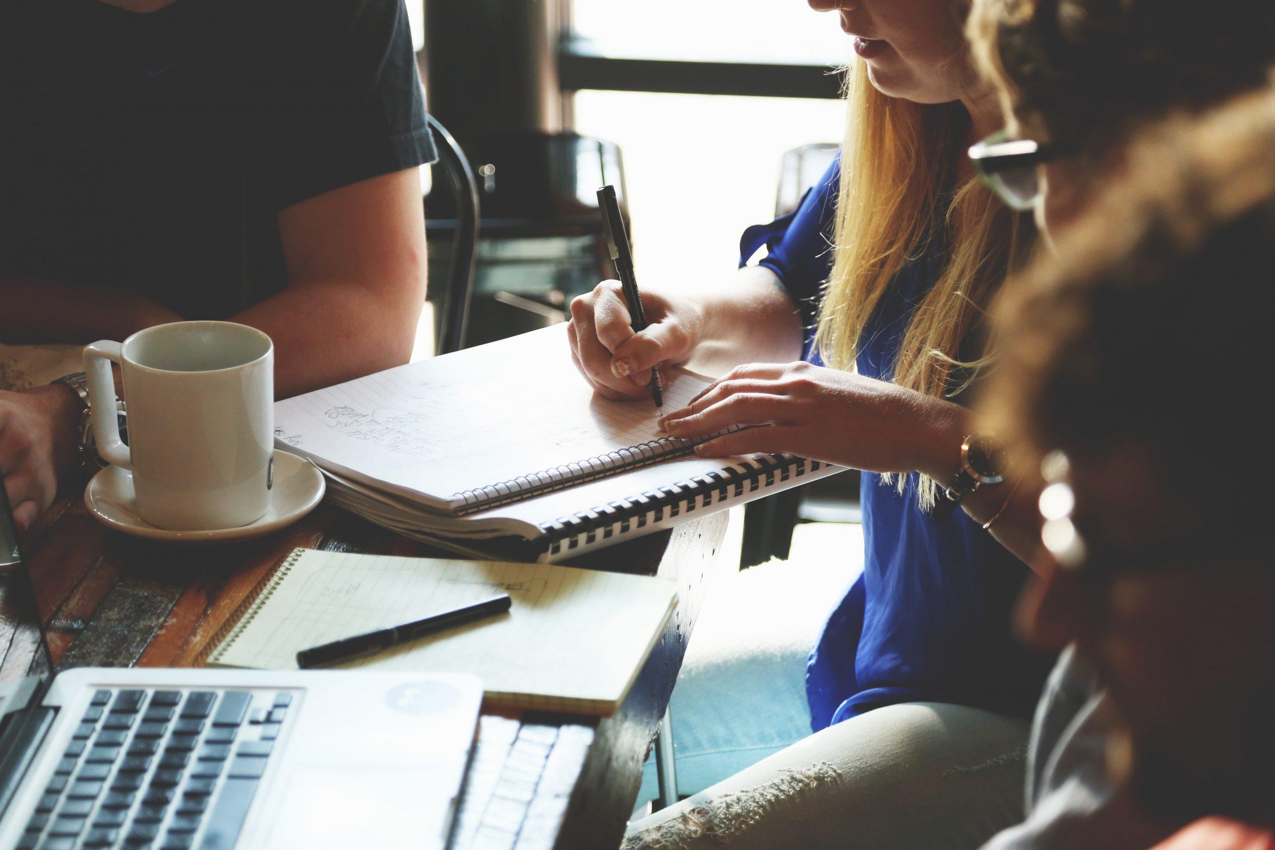 pessoas em uma mesa estudando segurando uma caneta sobre um caderno