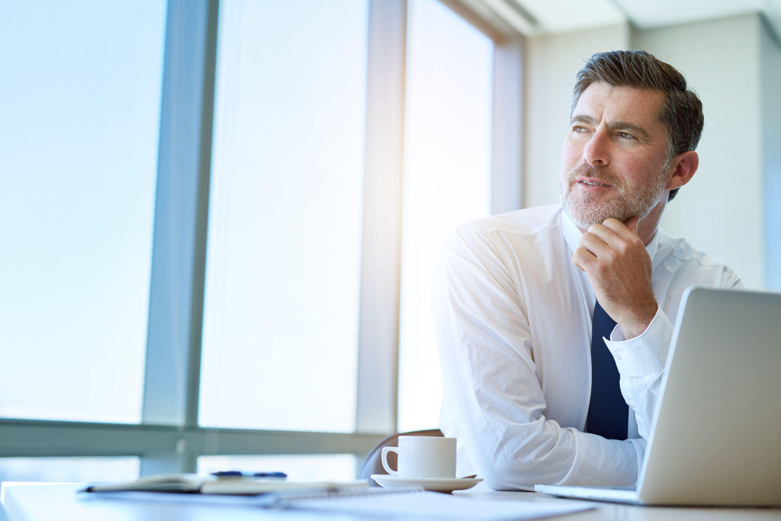 Homem de camisa social em frente ao computador pensando