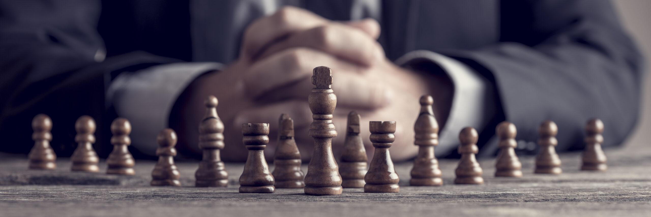mãos juntas com os dedos entrelançando e várias peças de xadrez a frente