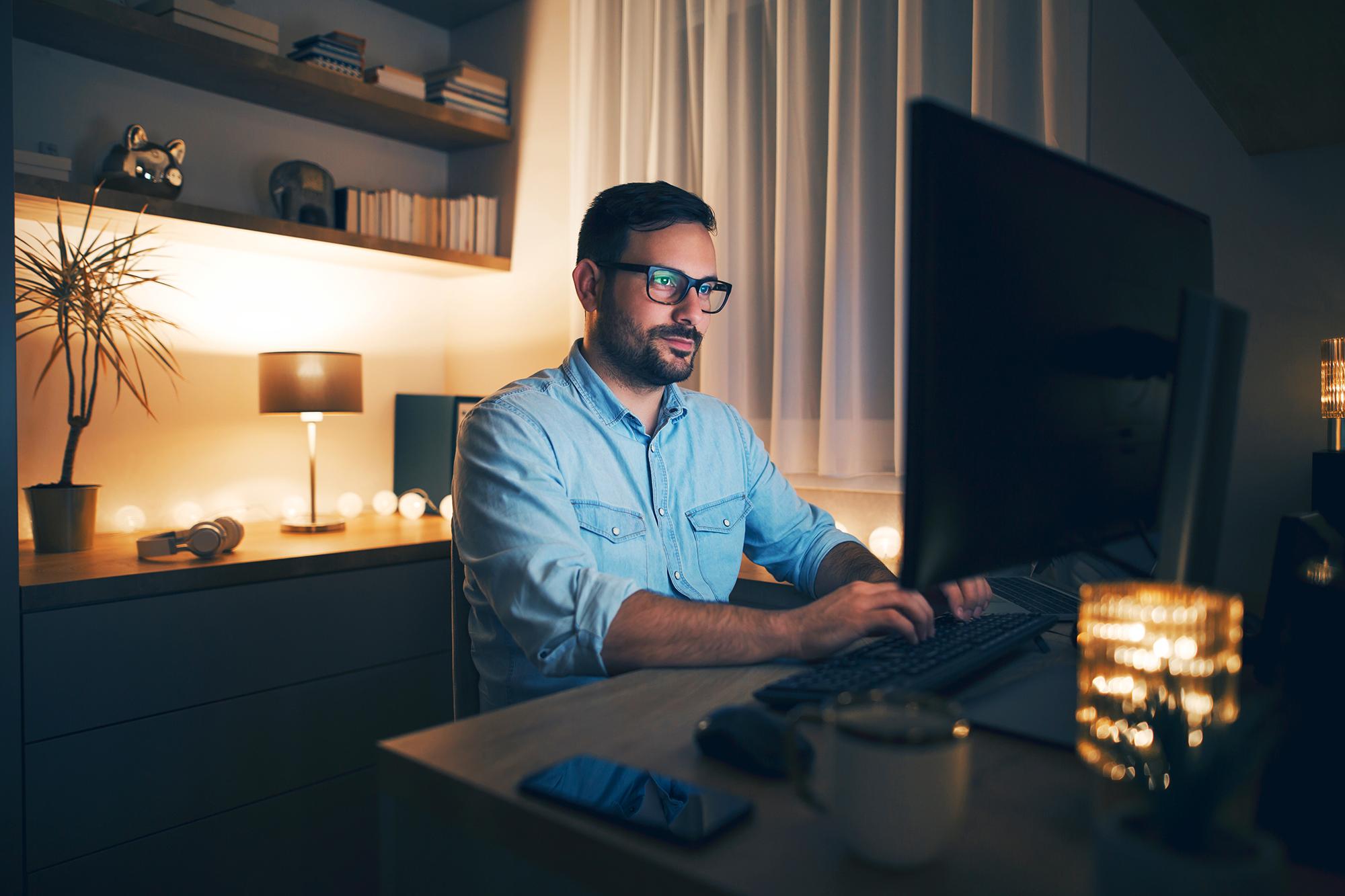 Homem de óculos mexendo em seu computador