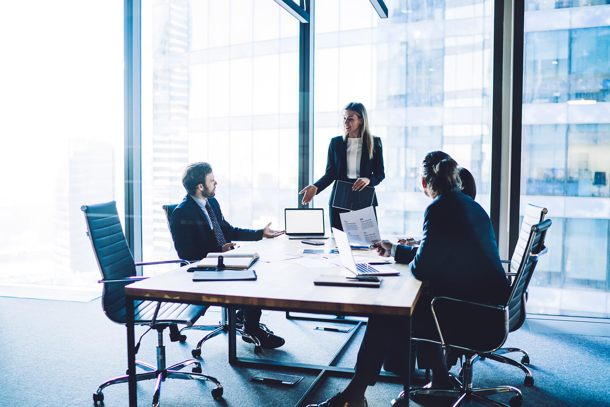 três pessoas em volta de uma mesa em reunião