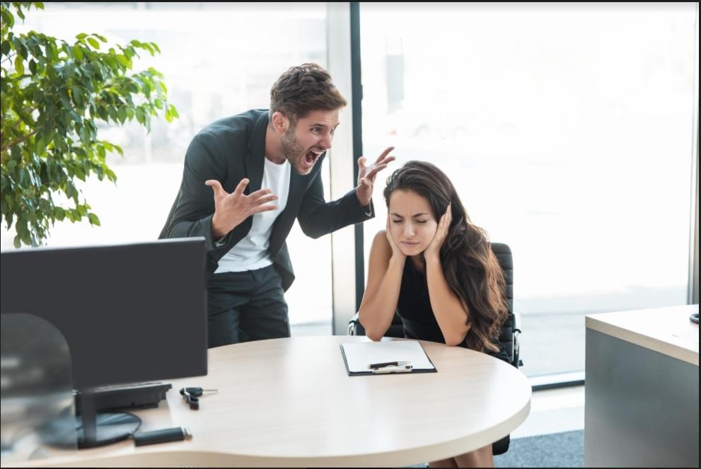 Homem gritando com uma mulher em um ambiente de trabalho