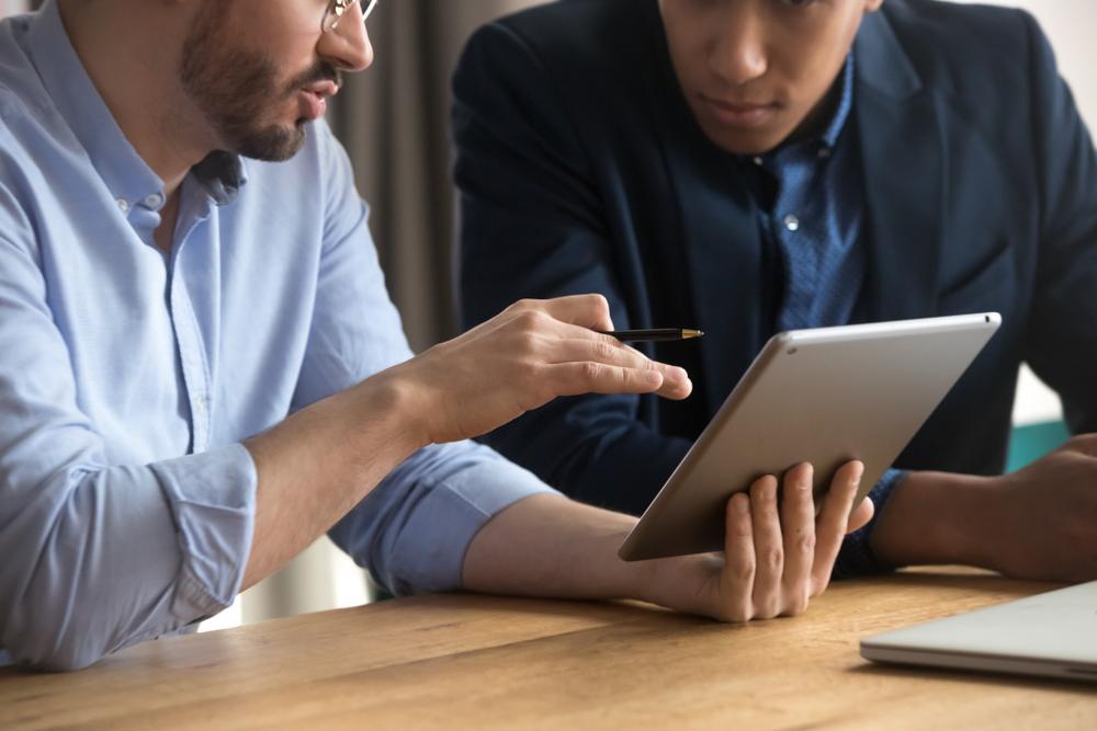 Dois vendedores conversando com um ipad na mão